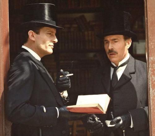 Jeremy Brett as Sherlock Holmes stands in a doorway talking to David Burke as Watson.