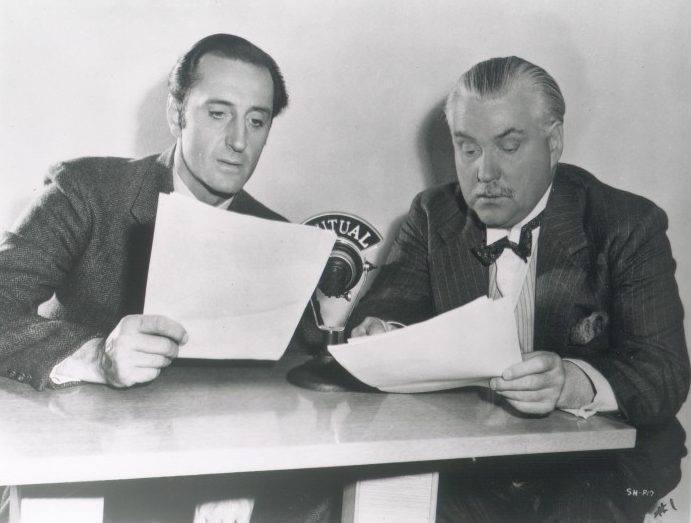 Two actors holding scripts sit in front of a microphone