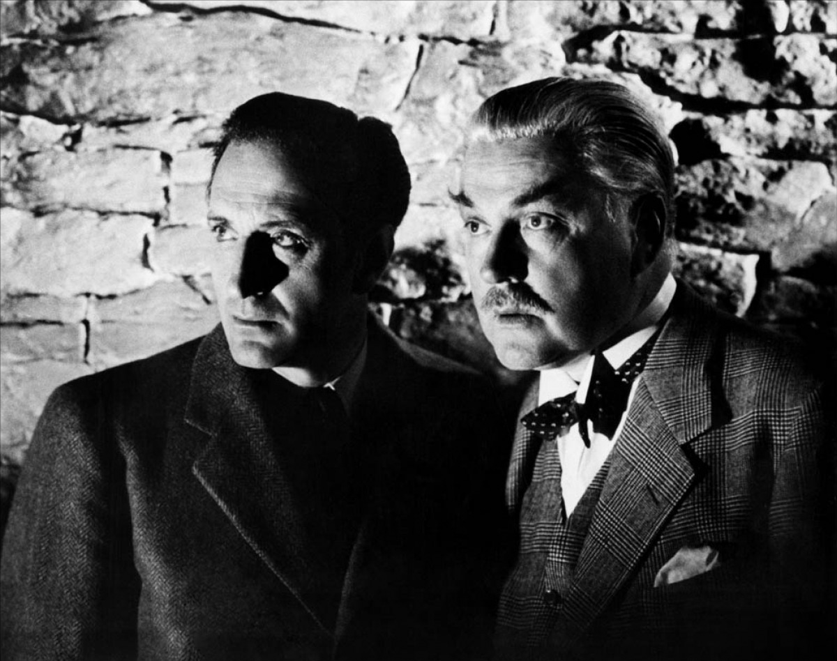 Basil Rathbone as Sherlock Holmes stands with Nigel Bruce as Dr. Watson.